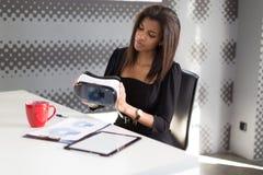 Dobra przyglądająca młoda biznesowa dama w czarnym silnym apartamencie siedzi przy biurowymi stołowymi chwyta vr szkłami Zdjęcia Royalty Free