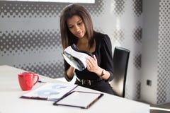 Dobra przyglądająca młoda biznesowa dama w czarnym silnym apartamencie siedzi przy biurowymi stołowymi chwyta vr szkłami Fotografia Stock