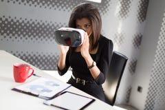 Dobra przyglądająca młoda biznesowa dama w czarnym silnym apartamencie siedzi przy biurowymi stołowymi chwyta vr szkłami Fotografia Royalty Free