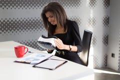 Dobra przyglądająca młoda biznesowa dama w czarnym silnym apartamencie siedzi przy biurowymi stołowymi chwyta vr szkłami Zdjęcia Stock