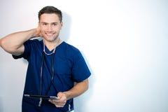 Dobra przyglądająca samiec lekarka, pielęgniarka w błękitnych pętaczkach lub, trzyma cyfrową pastylkę i śmiać się zdjęcie royalty free