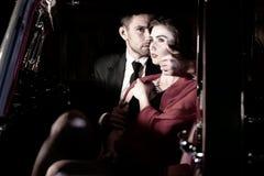 Dobra przyglądająca seksowna para, przystojny mężczyzna w kostiumu, piękna kobieta w czerwieni sukni, obejmuje żarliwie w rocznik zdjęcia royalty free
