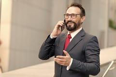Dobra transakcja! Brodaty biznesmen mówi telefonem i śmia się Widok Młody atrakcyjny biznesowy mężczyzna w szkłach używać smartph obrazy stock