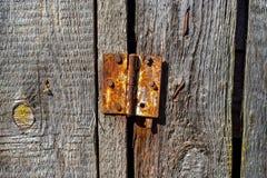 Dobradiça oxidada em uma porta velha de madeira Fotografia de Stock