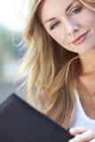 Dobrador ou menu louro novo bonito da leitura da mulher Fotografia de Stock Royalty Free