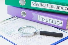 Dobradores coloridos, formulário limpo do seguro e uma lupa Fotos de Stock