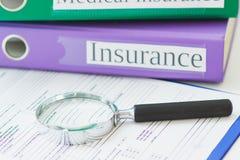 Dobradores coloridos, formulário limpo do seguro e uma lupa Fotografia de Stock Royalty Free