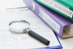 Dobradores coloridos, formulário limpo do seguro e uma lupa Imagens de Stock Royalty Free