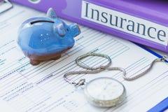 Dobradores coloridos, mealheiro, formulário limpo do seguro e um relógio de bolso Imagens de Stock