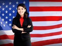 A dobradura da mulher de negócio cede a bandeira dos EUA imagens de stock