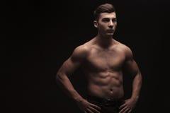 Dobramento masculino novo no fundo escuro do estúdio com mãos na cintura Fotografia de Stock Royalty Free