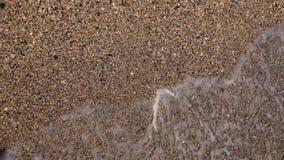 Dobramento transparente da água do mar na praia das conchas do mar Fim acima Movimento lento Vista superior filme