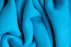 Dobras onduladas de pano azul do sumário do fundo da textura de matéria têxtil Fotos de Stock