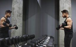 Dobrego przyglądającego młodego człowieka podnośni dumbbells przed lustrem obrazy stock