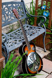 Dobro Style Guitar Leaning against Metal Bench. A Dobro-style acoustic guitar with sunburst finish leans against a metal-work bench in a garden stock image