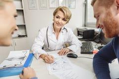 Dobrotliwa kobiety lekarka patrzeje pacjentów Obrazy Royalty Free