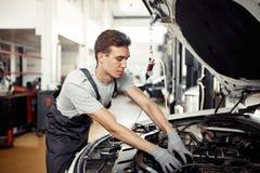 Dobry młody mechanik reparing pojazd przy jego pracą zdjęcia stock