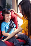 Dobry mamy uczepienia pas bezpieczeństwa syna obsiadanie w dziecku siedzi Obrazy Stock