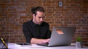 Dobry przyglądający caucasian urzędnika główkowanie, gryzienie i dotykamy przed komputerem z ściana z cegieł behind