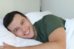 Dobry przyglądający etniczny mężczyzna ono uśmiecha się w łóżku fotografia stock