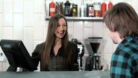 Dobry przyglądający kobiety barista bierze rozkaz od klienta z pastylka pokazem w ono uśmiecha się i sklep z kawą zbiory