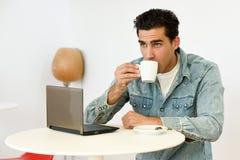 Dobry przyglądający mężczyzna jest ubranym drelichowego koszulowego obsiadanie w kawowym barze Fotografia Royalty Free