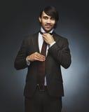 Dobry przyglądający mężczyzna przystosowywa jego krawat w kostiumu Zdjęcie Stock