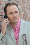 Dobry przyglądający przypadkowy urzędnik opowiada na telefonie komórkowym w ściana z cegieł biurze Obrazy Stock