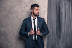 Dobry przyglądający przystojny biznesmen stoi w jego główkowaniu i biurze być ubranym kostium i krawat obraz stock