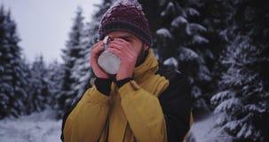 Dobry przyglądający turysta patrzeje prosto kamera po środku lasu w zima dniu podczas gdy pijący gorących napoje zbiory