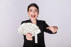 Dobrze ubierająca kobieta wskazuje palec przy gotówką, dolar Zdjęcia Stock