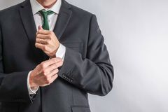 Dobrze ubierający biznesmen przystosowywa jego rękawy obraz stock