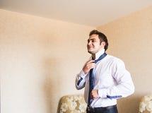 Dobrze ubierający biznesowy mężczyzna przystosowywa jego szyja krawat Fotografia Royalty Free