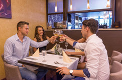 Dobrzy przyjaciele w restauracyjnych clink szkłach Zdjęcia Stock