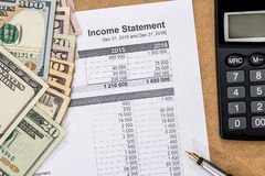 Doc与笔、计算器和金钱的收入报告 免版税图库摄影