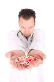 Doc and pills. Young doctor is offering to you bunch of different pills as medication for your good health isolated on the white background (shallow dept Royalty Free Stock Photos
