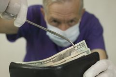 Doc-wallet. Doctor extracting money from wallet with forceps Royalty Free Stock Photos