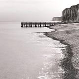 Doca no mar e penhascos rochosos na praia da rocha do beira-mar Fotografia de Stock