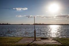 Doccia arrugginita su una spiaggia che affronta l'acqua blu del lago Palic, in Subotica, la Serbia, durante il tramonto di estate immagini stock