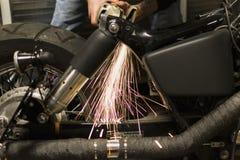 Doccia delle scintille bianco calde dalla lacuna di riempimento della smerigliatrice nel motorcycl Fotografie Stock