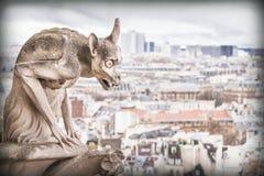 Doccione (chimera), demoni di pietra, con la città di Parigi su fondo Fotografia Stock