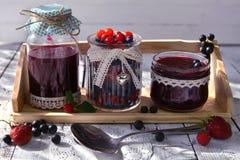 Doce caseiro nos frascos de vidro com colher e as bagas frescas na tabela de madeira Imagem de Stock