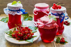 Doce caseiro preservado do corinto vermelho nos frascos de vidro na tabela de madeira branca Bagas frescas e folhas verdes, placa Imagem de Stock