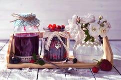 Doce da baga nos frascos de vidro do vintage decorados com fitas e as rosas selvagens Fotos de Stock