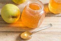 Doce da geleia de Apple na tabela de madeira com maçãs - foco seletivo sobre imagens de stock