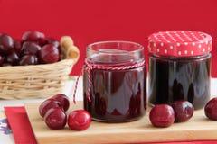 Doce de cereja caseiro em uns frascos de vidro pequenos Cerejas frescas no fundo Fotos de Stock