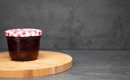 Doce de cereja em um frasco de vidro com uma tampa vermelha e branca fechado em uma placa de madeira Fundo cinzento Geleia da cer foto de stock royalty free