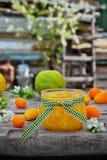 Doce de fruta alaranjado em um frasco de vidro com fruto fresco Foto de Stock Royalty Free
