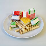 Doce de fruta colorido cortado nas partes em uma placa branca Imagens de Stock