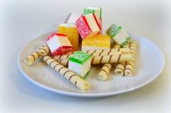 Doce de fruta colorido cortado nas partes em uma placa branca Foto de Stock